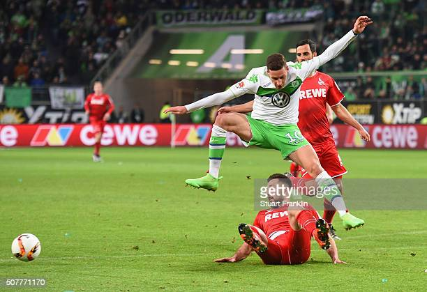 Julian Draxler of VfL Wolfsburg is tackled by Dominic Maroh of Cologne during the Bundesliga match between VfL Wolfsburg and 1 FC Koeln at Volkswagen...
