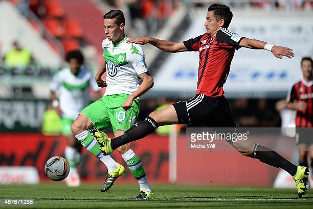 Julian Draxler of Wolfsburg is challenged by Benjamin Huebner of Ingolstadt during the Bundesliga match between FC Ingolstadt and VfL Wolfsburg at...