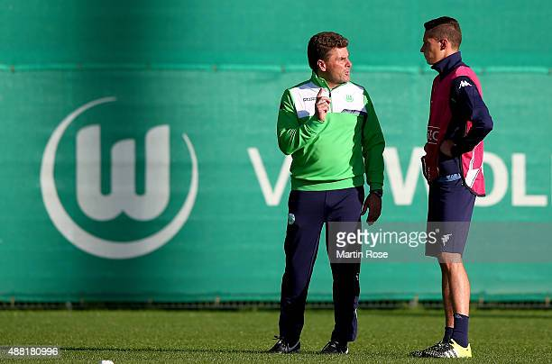 Julian Draxler of Wolfsburg talks to head coach Dieter Hecking during a training sessiosn ahead of the UEFA Champions League group B match between...
