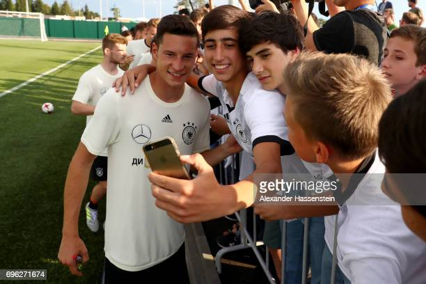 Julian Draxler poses for a selfie with a fan after the first training session at Park Arena training ground on June 15 2017 in Sochi Russia