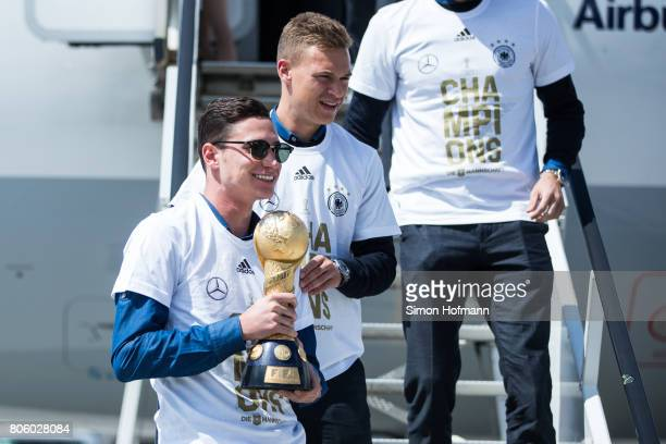 Julian Draxler presents the trophy as he departs the plane carrying the Germany National Football Team during the arrival at Frankfurt International...