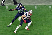 Julian Edelman of the New England Patriots breaks the tackle of Tharold Simon of the Seattle Seahawks in Super Bowl XLIX February 1 2015 at the...