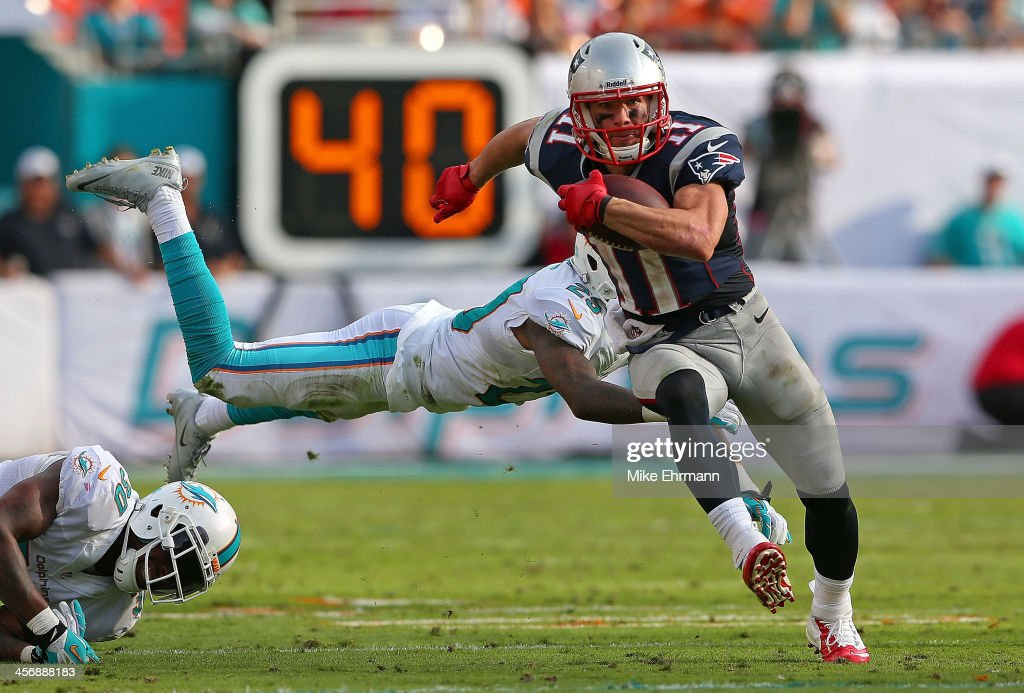 <a gi-track='captionPersonalityLinkClicked' href=/galleries/search?phrase=Julian+Edelman&family=editorial&specificpeople=4489543 ng-click='$event.stopPropagation()'>Julian Edelman</a> #11 of the New England Patriots escapes a tackle from <a gi-track='captionPersonalityLinkClicked' href=/galleries/search?phrase=Nolan+Carroll&family=editorial&specificpeople=5574471 ng-click='$event.stopPropagation()'>Nolan Carroll</a> #28 of the Miami Dolphins during a game at Sun Life Stadium on December 15, 2013 in Miami Gardens, Florida.