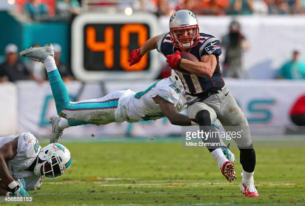 Julian Edelman of the New England Patriots escapes a tackle from Nolan Carroll of the Miami Dolphins during a game at Sun Life Stadium on December 15...