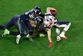 Julian Edelman of the New England Patriots gets tackled by Tharold Simon of the Seattle Seahawks in Super Bowl XLIX February 1 2015 at the University...