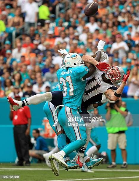 Julian Edelman of the New England Patriots has a pass blocked by Michael Thomas of the Miami Dolphins during a game at Hard Rock Stadium on January 1...