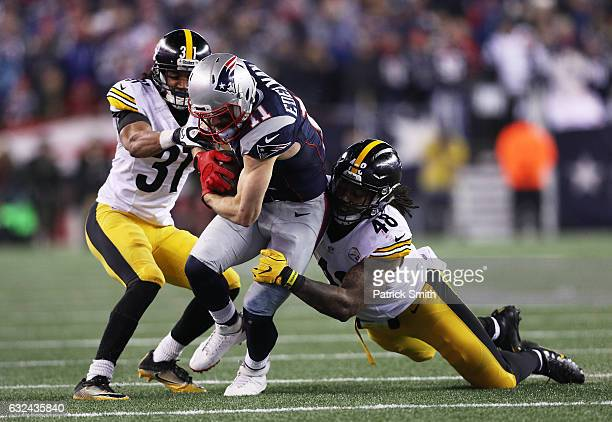 Julian Edelman of the New England Patriots is tackled by Ross Cockrell and Bud Dupree of the Pittsburgh Steelers during the fourth quarter in the AFC...