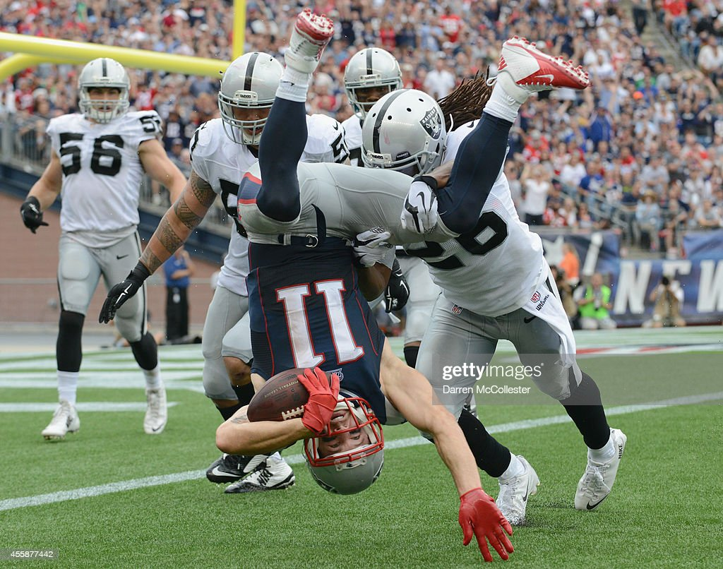 <a gi-track='captionPersonalityLinkClicked' href=/galleries/search?phrase=Julian+Edelman&family=editorial&specificpeople=4489543 ng-click='$event.stopPropagation()'>Julian Edelman</a> #11 of the New England Patriots is tackled during the fourth quarter against the Oakland Raiders at Gillette Stadium on September 21, 2014 in Foxboro, Massachusetts.