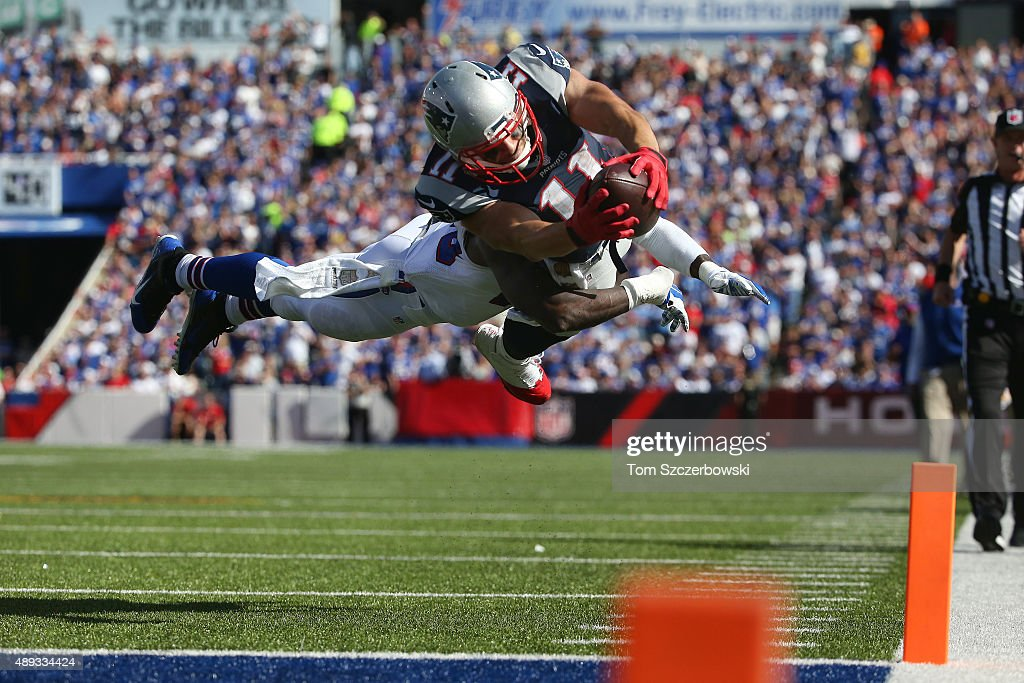 Julian Edelman of the New England Patriots scores a touchdown during NFL game action as Aaron Williams of the Buffalo Bills tries to make the tackle...