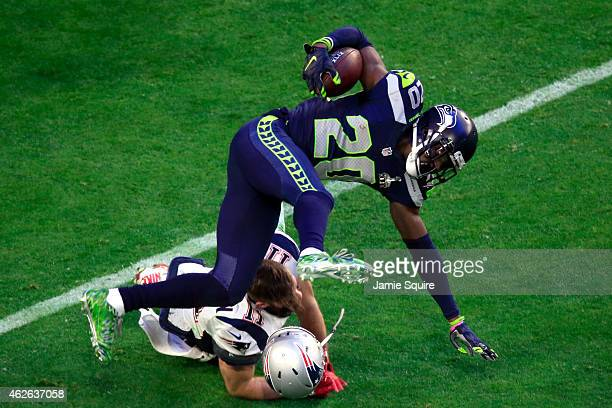Julian Edelman of the New England Patriots tackles Jeremy Lane of the Seattle Seahawks after an interception in the first quarter during Super Bowl...