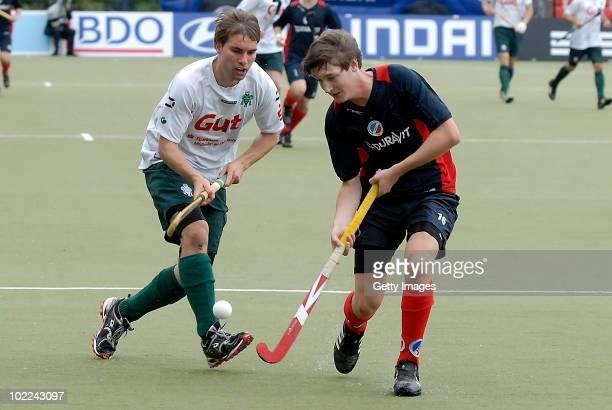 Julian Fischer of Mannheim battles for fhe hockey ball with Johannes Schmitz of Muehlheim during the men's 3rd/4th place match between Mannheimer HC...