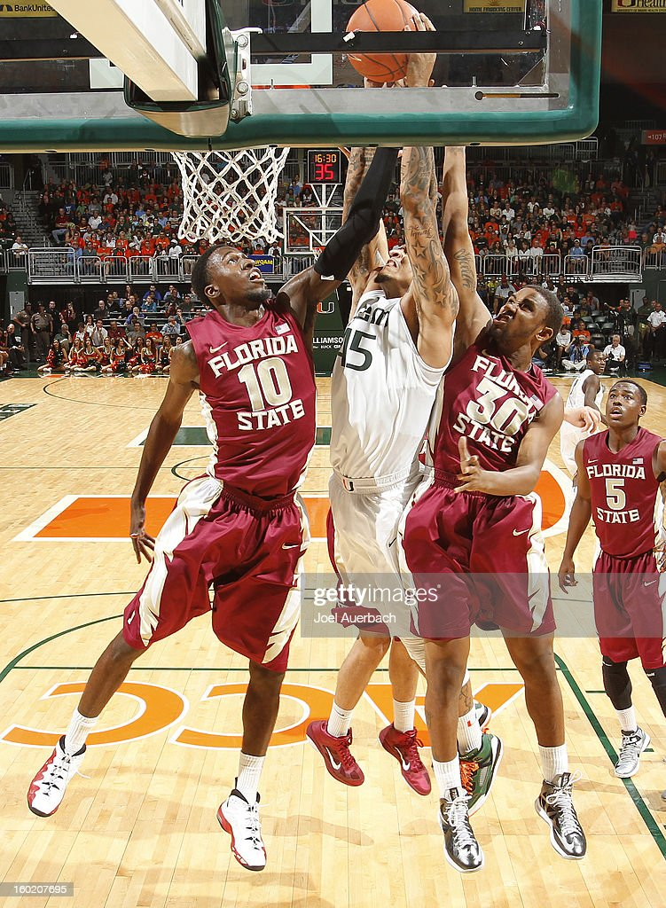 Julian Gamble #45 of the Miami Hurricanes scores between Okaro White #10 and Ian Miller #30 of the Florida State Seminoles on January 27, 2013 at the BankUnited Center in Coral Gables, Florida. The Hurricanes defeated the Seminoles 71-47.