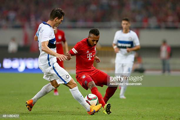 Julian Green of Muenchen battles for the ball with Enrico Baldini of Milan during the international friendly match between FC Bayern Muenchen and...