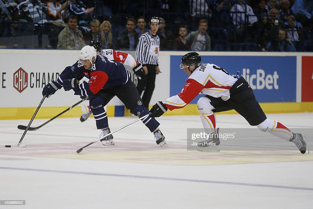 Julian Jakobsen (L) of Hamburg and Per Nagander-Savilahti of Lulea compete for the puck during the Champions Hockey League group stage game between Hamburg Freezers and Lulea Hockey on August 22, 2014 in Hamburg, Germany.