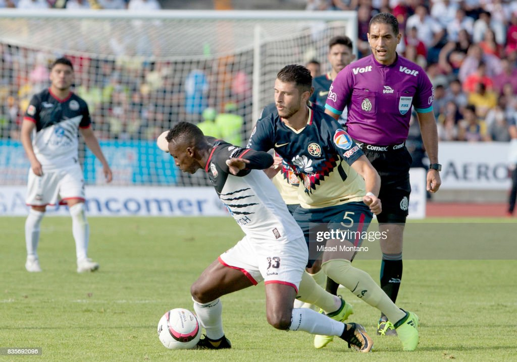Julian Quiñones of Lobos BUAP competes for the ball with Guido Rodriguez of America during the fifth round match between Lobos BUAP and America as part of the Torneo Apertura 2017 Liga MX at Olimpico de la BUAP Stadium on August 19, 2017 in Puebla, Mexico.