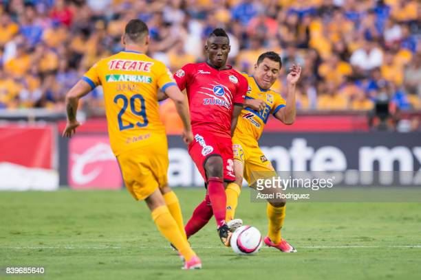 Julian Quiñones of Lobos fights for the ball with Jesus Dueñas and Alberto Acosta of Tigres during the seventh round match between Tigres UANL and...