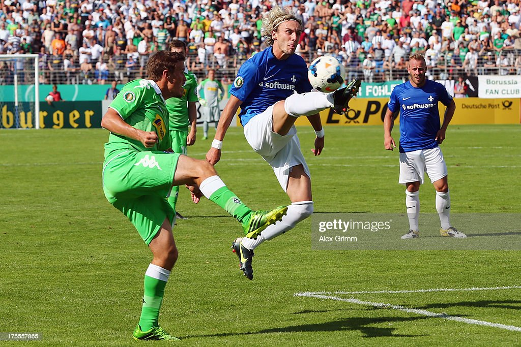 Julian Ratei (C) of Darmstadt clears the ball ahead of <a gi-track='captionPersonalityLinkClicked' href=/galleries/search?phrase=Max+Kruse&family=editorial&specificpeople=3945507 ng-click='$event.stopPropagation()'>Max Kruse</a> of Moenchengladbach during the DFB Cup first round match between Darmstadt 98 and Borussia Moenchengladbach at Boellenfalltorstadion on August 4, 2013 in Darmstadt, Germany.