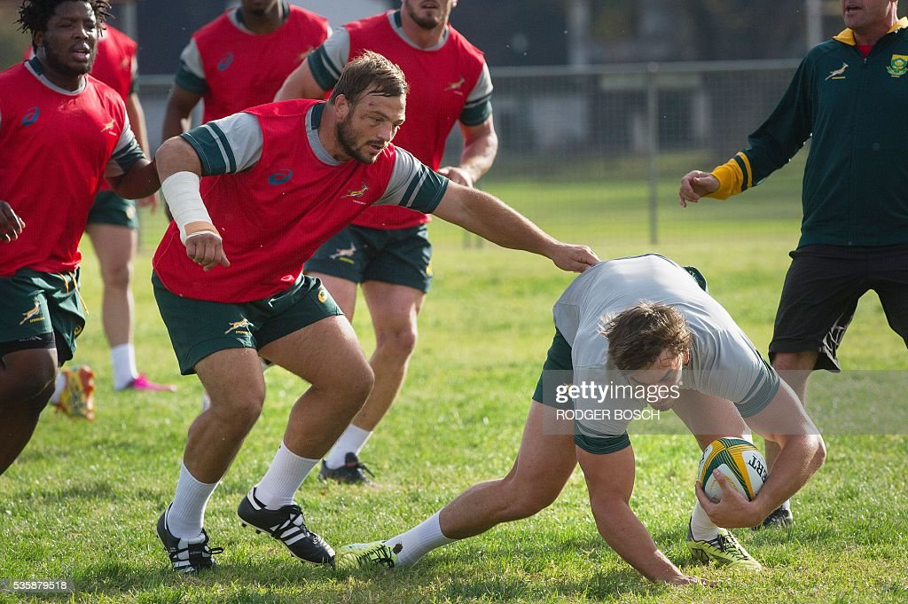 Julian Redelinghuys (C,L) tackles Eben Etsebeth (R) during a South Africa's national rugby team Springbok training after the announcement of the new captain appointment on 30 May, 2016 in Stellenbosch, near Cape town. Adriaan Strauss will captain South Africa in a three-Test home series against Ireland during June, new national coach Allister Coetzee announced Monday in Stellenbosch near Cape Town. / AFP / RODGER