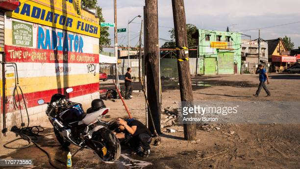 Julian Rodriguez washes his motorcycle after a day of work on June 17 2013 in the Willet's Point neighborhood of the Queens borough of New York City...