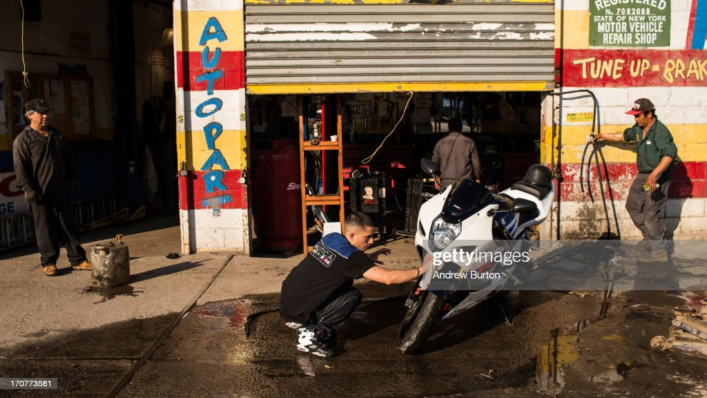 Julian Rodriguez washes his motorcycle after a day of work on June 17, 2013 in the Willet's Point neighborhood of the Queens borough of New York City. The Willet's Point Neighborhood, also known as the Iron Triangle, is situated directly next to Citi Field, where the Met's play baseball, and is known for both its car repair shops and lack of paved roads. The future of the neighborhood has been a contentious issue between residents and the city, as the city hopes to further develop the land despite protests from its residents.