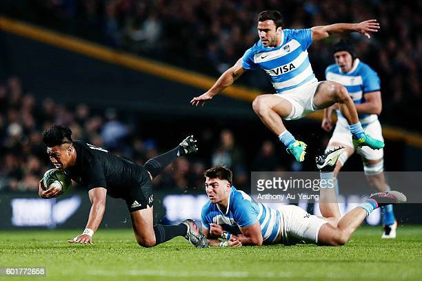 Julian Savea of New Zealand charges through Facundo Isa and Martin Landajo of Argentina during the Rugby Championship match between the New Zealand...