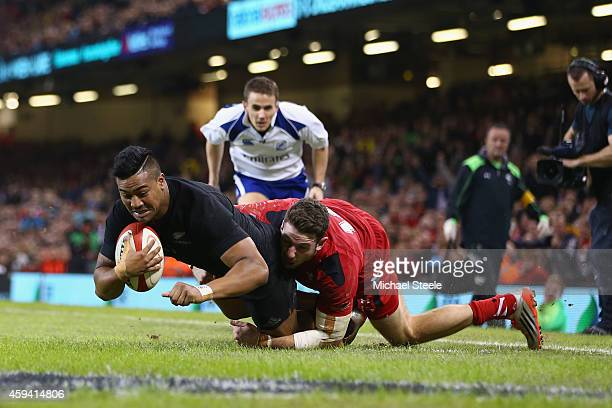 Julian Savea of the All Blacks scores his sides opening try despite the challenge from Alex Cuthbert of Wales during the International match between...