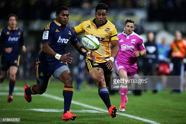 Julian Savea of the Hurricanes and Waisake Naholo of the Highlanders chase after the ball during the round 17 Super Rugby match between the...