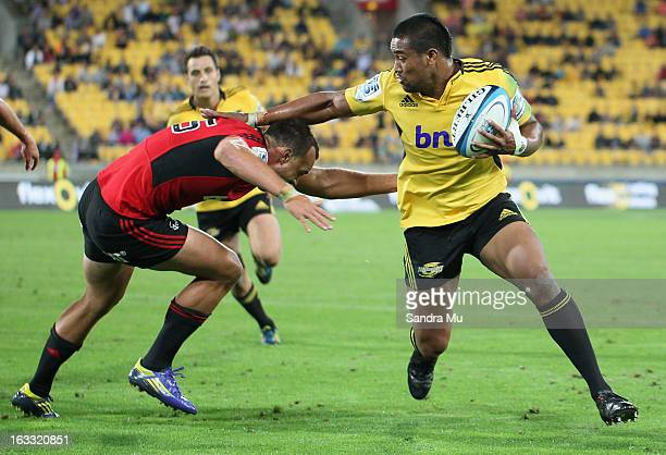Julian Savea of the Hurricanes fends off Israel Dagg of the Crusaders during the round four Super Rugby match between the Hurricanes and the...