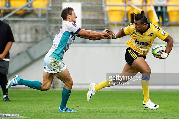 Julian Savea of the Hurricanes fends off Johan Goosen of the Cheetahs during the round five Super Rugby match between the Hurricanes and the Cheetahs...