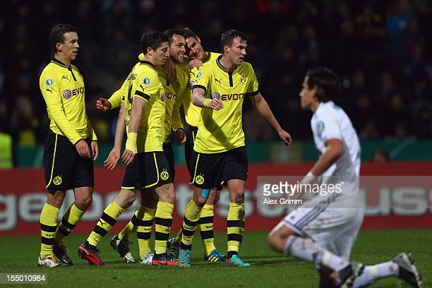Julian Schieber of Dortmund celebrates his team's fourth goal with team mates as goalkeeper Jasmin Fejzic of Aalen reacts during the second round...