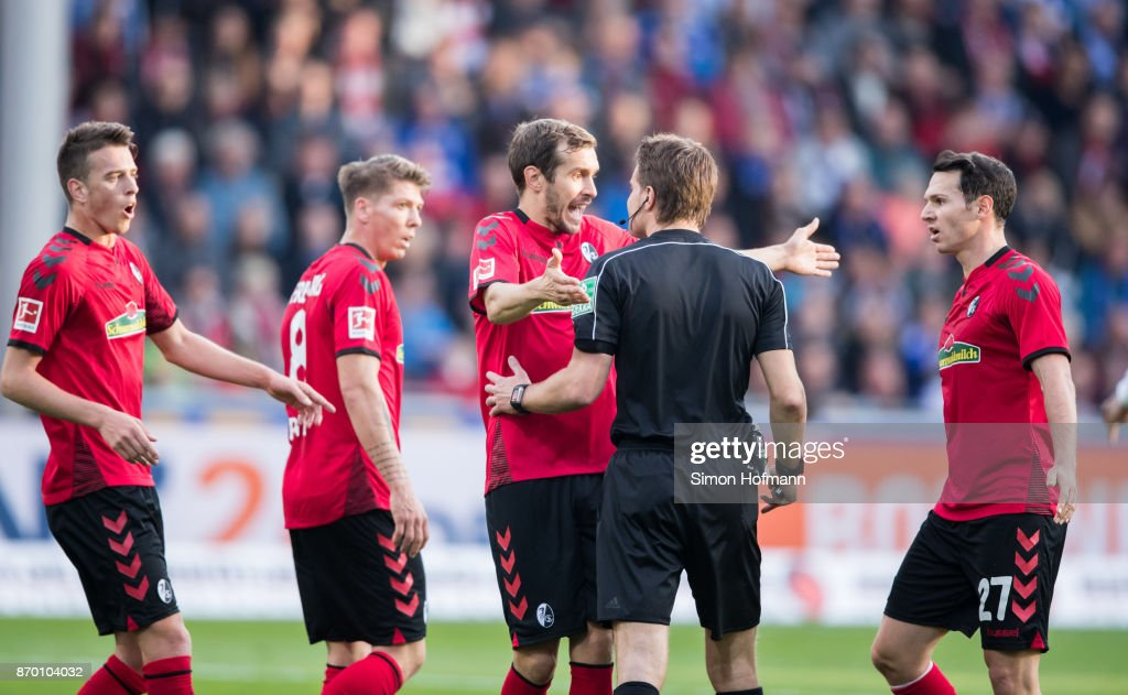 Julian Schuster (C) of Freiburg argues with referee Felix Brych during the Bundesliga match between Sport-Club Freiburg and FC Schalke 04 at Schwarzwald-Stadion on November 4, 2017 in Freiburg im Breisgau, Germany.