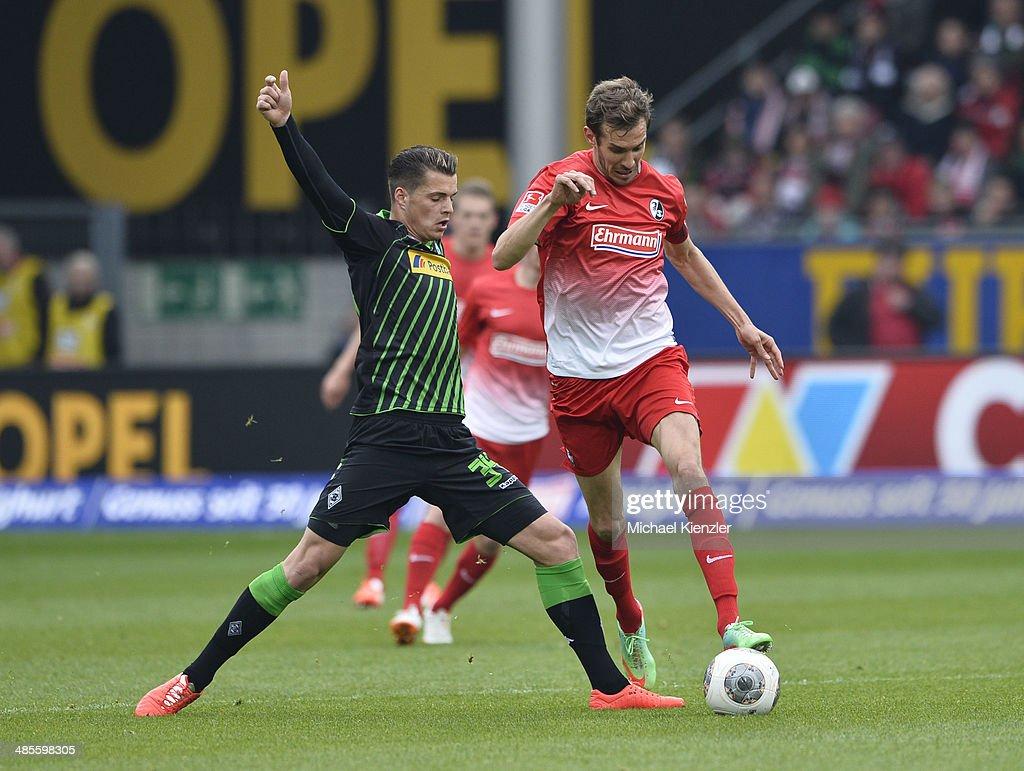 Julian Schuster (R) of Freiburg challenges Granit Xhaka during the Bundesliga match between SC Freiburg and Borussia Moenchengladbach at Mage Solar Stadium on April 19, 2014 in Freiburg, Germany.