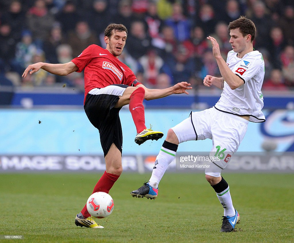 Julian Schuster of Freiburg (L) challenges Havard Nordtveit during the Bundesliga match between SC Freiburg and VfL Borussia Moenchengladbach at MAGE SOLAR Stadium on March 30, 2013 in Freiburg, Germany.