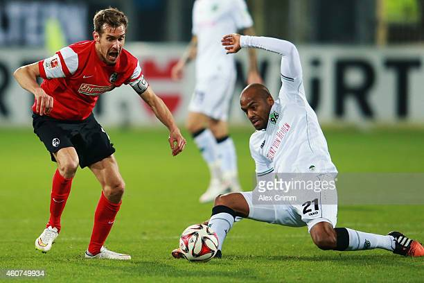 Julian Schuster of Freiburg is challenged by Jimmy Briand of Hannover during the Bundesliga match between SC Freiburg and Hannover 96 at...