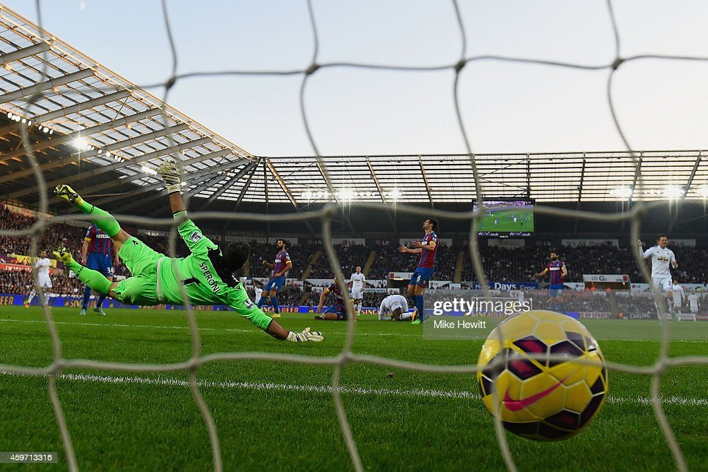 Julian Speroni of Crystal Palace dives but fails to stop Wilfried Bony of Swansea City from scoring their first goal during the Barclays Premier...