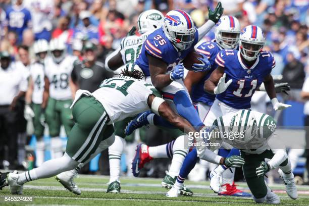 Julian Stanford and Marcus Maye both of the New York Jets attempt to tackle Mike Tolbert of the Buffalo Bills during the first half on September 10...
