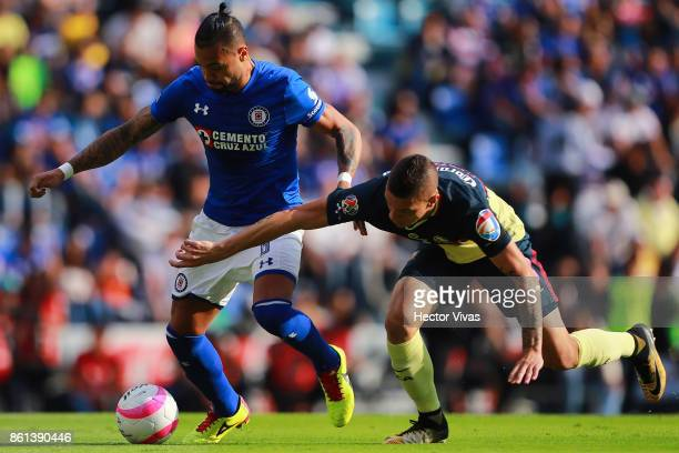 Julian Velazquez of Cruz Azul struggles for the ball with Mateus Uribe of America during the 13th round match between Cruz Azul and America as part...