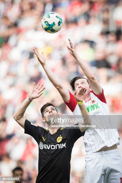 Julian Weigl of Borussia Dortmund and Michael Gregoritsch of Augsburg try to catch the ball during the Bundesliga match between FC Augsburg and...