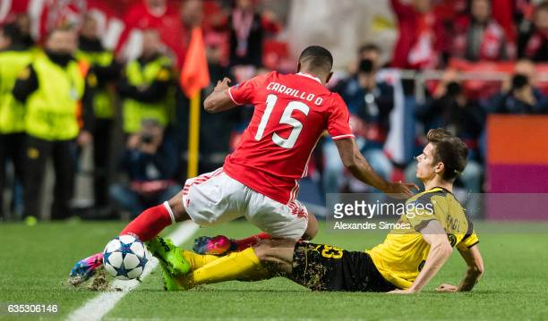 Julian Weigl of Borussia Dortmund challenges Andre Carrillo of SL Benfica during the UEFA Champions League Round of 16 First Leg match between SL...