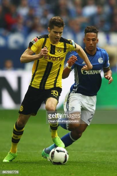 Julian Weigl of Borussia Dortmund gets past the tackle from Thilo Kehrer of Schalke during the Bundesliga match between FC Schalke 04 and Borussia...