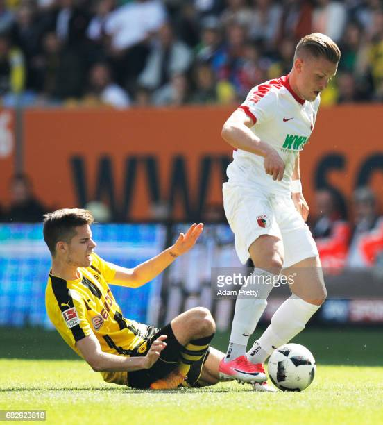 Julian Weigl of Borussia Dortmund is seriously injured while being challenged by Philipp Max of Augsburg during the Bundesliga match between FC...