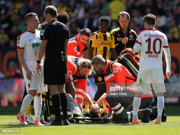 Julian Weigl of Borussia Dortmund is taken off on a stretcher after being seriously injured while being challenged by Philipp Max of Augsburg during...