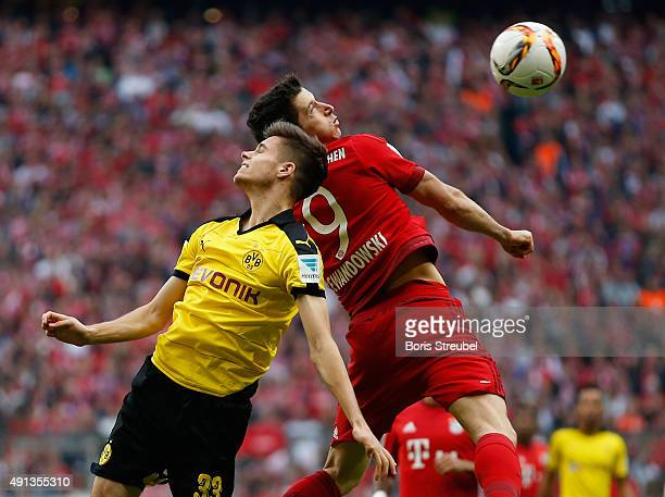 Julian Weigl of Borussia Dortmund jumps for a header with Robert Lewandowski of Bayern Muenchen during the Bundesliga match between FC Bayern...