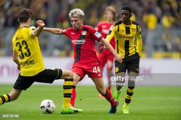 Julian Weigl of Dortmund and Kevin Kampl of Bayer Leverkusen Ousmane Dembele of Dortmund battle for the ball during the Bundesliga match between...
