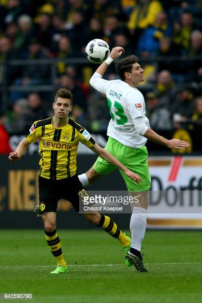 Julian Weigl of Dortmund and Mario Gomez of Wolfsburg go up for a header during the Bundesliga match between Borussia Dortmund and VfL Wolfsburg at...