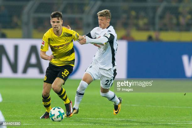 Julian Weigl of Dortmund and Mickael Cuisance of Moenchengladbach battle for the ball during the Bundesliga match between Borussia Dortmund and...