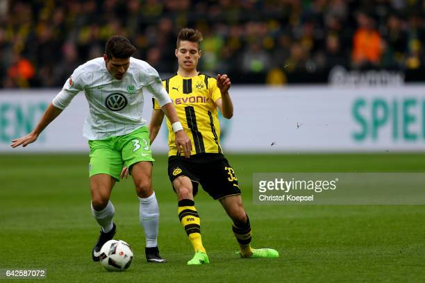 Julian Weigl of Dortmund challenges Mario Gomez of Wolfsburg during the Bundesliga match between Borussia Dortmund and VfL Wolfsburg at Signal Iduna...