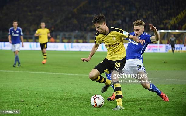 Julian Weigl of Dortmund is challenged by Felix Platte of Schalke during the Bundesliga match between Borussia Dortmund and FC Schalke 04 at Signal...