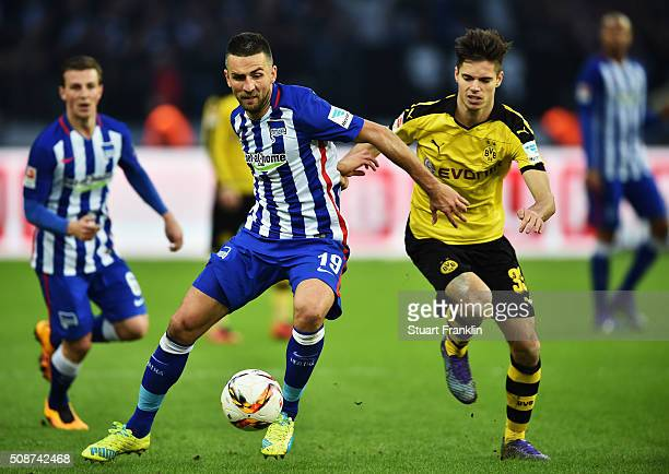 Julian Weigl of Dortmund is challenged by Vedad Ibisevic of Berlin during the Bundesliga match bewteen Hertha BSC and Borussia Dortmund at...