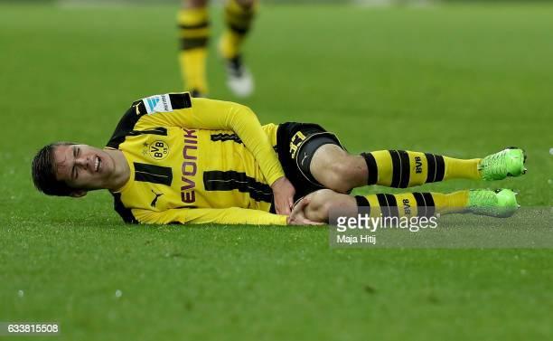 Julian Weigl of Dortmund lies injured on the pitch during the Bundesliga match between Borussia Dortmund and RB Leipzig at Signal Iduna Park on...